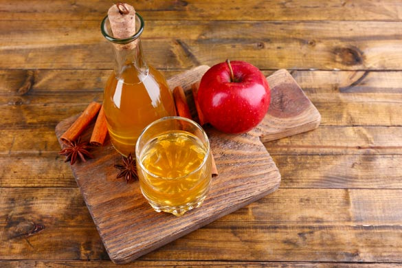 Apple-cider-in-glass-bottle-with-cinnamon-sticks-and-fresh-apples-on-cutting-board