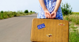 young girl on the road with a suitcase