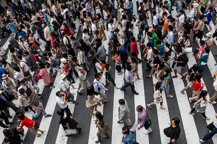 Crowds of people walk across a pedestrian crosswalk in the downtown business district in Osaka, Japan.