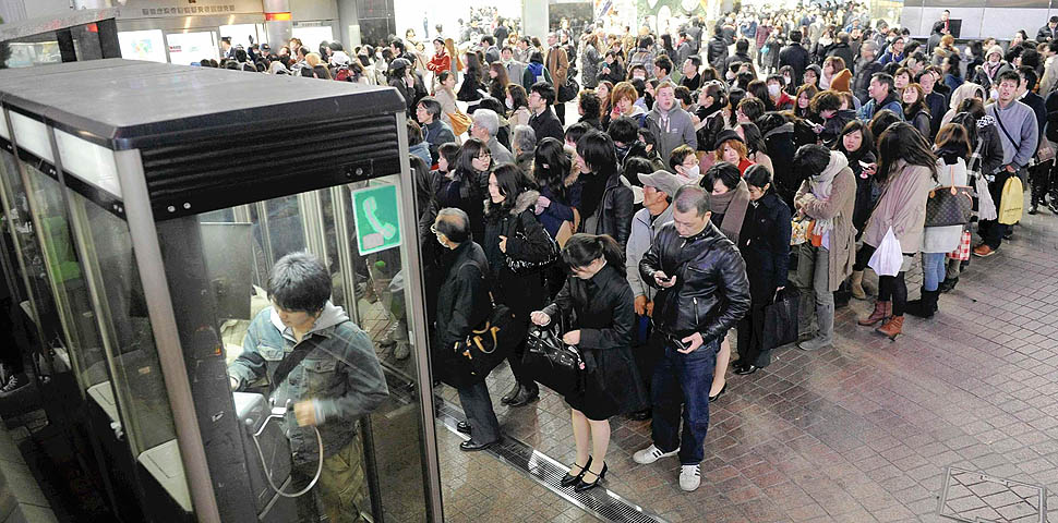 People line up in front of public telephone booths at Shibuya station in Tokyo March 11, 2011. The biggest earthquake to hit Japan since records began 140 years ago struck the northeast coast on Friday, triggering a 10-metre tsunami that swept away everything in its path, including houses, ships, cars and farm buildings on fire. REUTERS/YOMIURI(JAPAN - Tags: DISASTER) FOR EDITORIAL USE ONLY. NOT FOR SALE FOR MARKETING OR ADVERTISING CAMPAIGNS. JAPAN OUT. NO COMMERCIAL OR EDITORIAL SALES IN JAPAN. YES