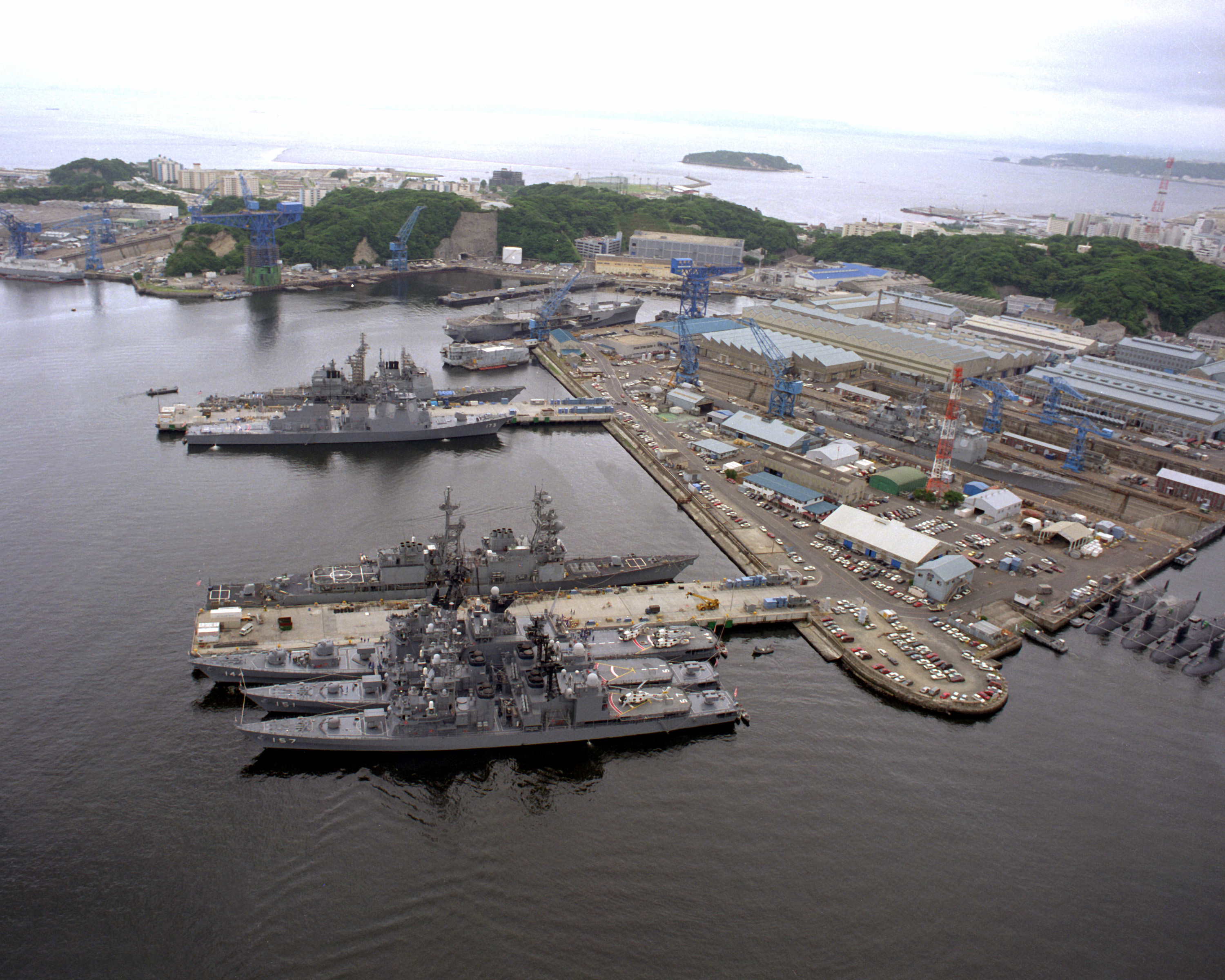 An aerial view of the U.S. Naval Ship Repair Facility at the naval base. The ships tied up at the piers are (b. to t) the Japanese Maritime Self-Defense Force destroyers SAWAGIRI (DD-157), ASAGIRI (DD-151), the helicopter carrying destroyer KURAMA (DDH-144), the destroyer USS O'BRIEN (DD-975), the Japanese guided missile destroyer KONGO (DDG-173) and a Ticonderoga class guided missile cruiser. At the top, off to the right, is the amphibious command ship USS BLUE RIDGE (LCC-19). To the far right at Berth 5 is four Japanese Yushio class submarines.